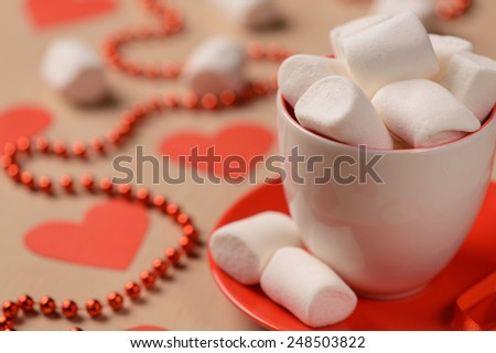 Happy valentines day. Closeup of the cup full of white marshmallows placed on the table with decorative red hearts and red festive beads