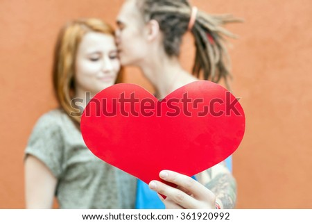 Happy Valentines Day couple holding red heart symbol and kissing, 14th February celebration, Valentine. Love concept.