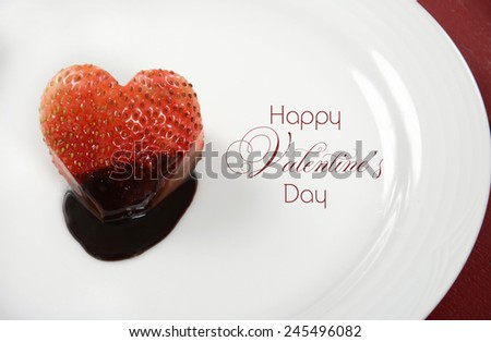 Happy Valentines Day heart shape red strawberry dipped in dark chocolate on round white plate on red wood background, with sample text. - stock photo