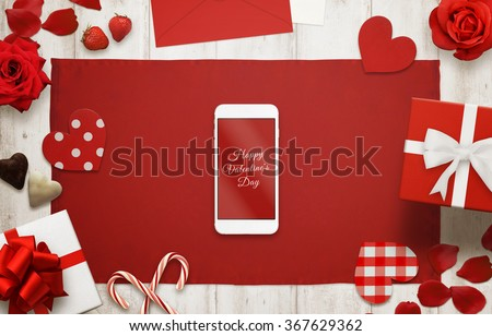 Happy Valentines day on smart phone display. Table cloth on wooden background. Love scene with hearts, gift, candle, petals, rose - stock photo