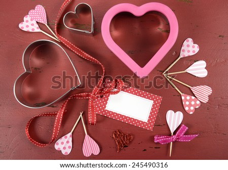 Happy Valentines Day red vintage wood background with heart shape cookie cutters and cupcake toppers with gift tag. - stock photo