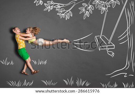 Happy valentines love story concept of a romantic couple against chalk drawings background. Male catching his girlfriend jumping from tree swings. - stock photo