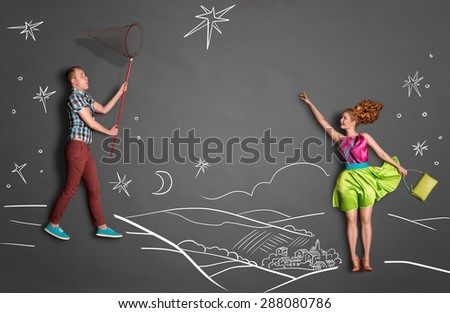 Happy valentines love story concept of a romantic couple catching stars with a butterfly net against chalk drawings background of a night sky. - stock photo