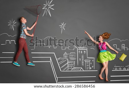 Happy valentines love story concept of a romantic couple catching stars with a butterfly net on the roof against chalk drawings background of a night sky.
