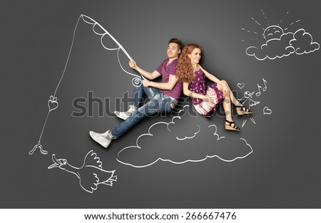 Happy valentines love story concept of a romantic couple fishing on a cloud with a bait on a hook against chalk drawings background. - stock photo