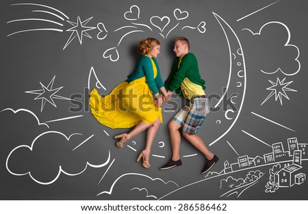 Happy valentines love story concept of a romantic couple sitting on the moon and holding hands against chalk drawings background of a night sky.