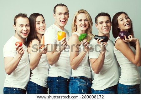 Happy veggies concept. Group portrait of healthy boys and girls in white t-shirts, sleeveless shirts and blue jeans standing with vegetables & posing over gray background. Urban style. Studio shot - stock photo