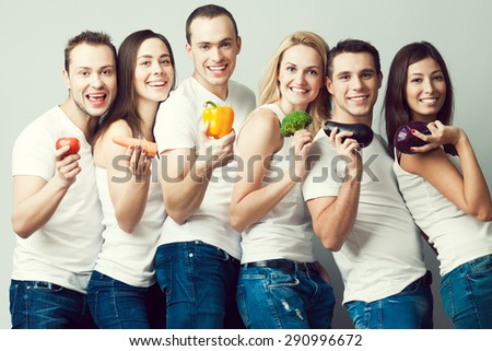 Happy veggies concept. Group portrait of healthy boys and girls in white t-shirts, sleeveless shirts and blue jeans standing with vegetables & posing over gray background. Urban style. Studio shot