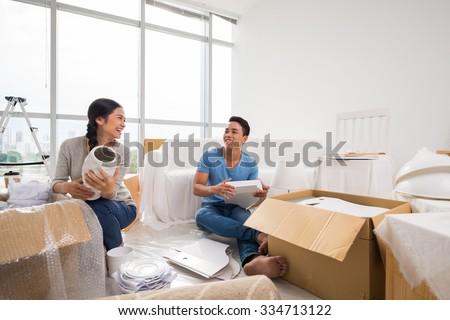 Happy Vietnamese family laughing when unpacking belongings - stock photo