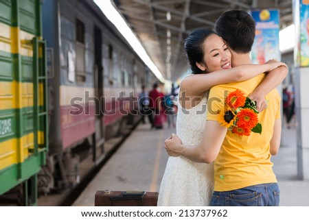 Happy Vietnamese girl hugging her boyfriend at the railway station - stock photo