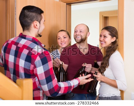 Happy visitors with bottles standing in doorway and smiling - stock photo