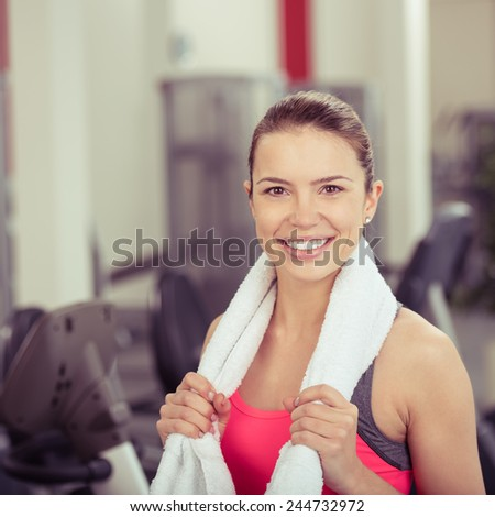 Happy vivacious attractive young woman in a gym standing with a towel around her shoulders smiling at the camera, head and shoulders - stock photo