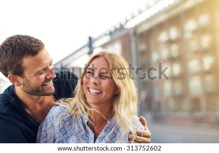 Happy vivacious romantic young couple enjoying a good joke hugging and laughing merrily as they stand outdoors on am urban residential street