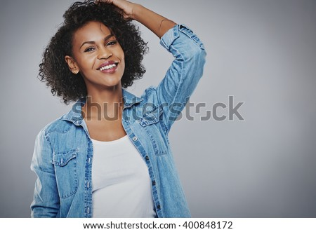 Happy vivacious young African American woman with curly hair standing with her hand to her head looking at the camera with a lovely warm friendly smile, over grey with copy space - stock photo