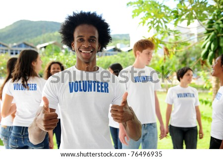 happy volunteer african american man showing thumbs up sign and group - stock photo