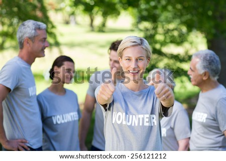 Happy volunteer blonde with thumbs up on a sunny day - stock photo