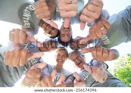 Happy volunteer family looking down with thumbs up on a sunny day - stock photo