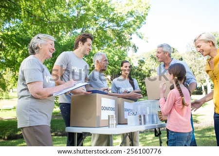 Happy volunteer family separating donations stuffs on a sunny day - stock photo