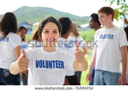 happy volunteer girl showing thumbs up sign, group in background - stock photo