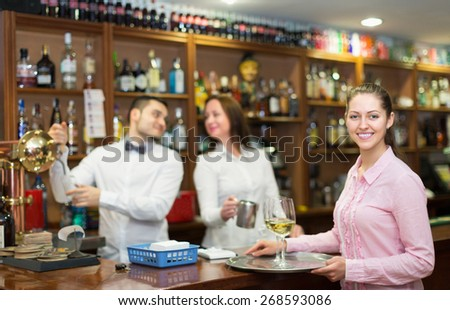 Happy waitress and barmen working in modern bar - stock photo