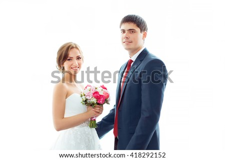 Happy wedding couple in love. Beautiful bride in white dress with brides bouquet and handsome groom in blue suit standing looking to the camera indoors at home against big window, white bright - stock photo
