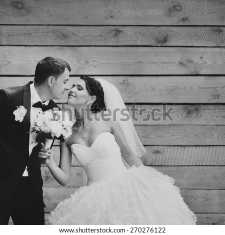 Happy wedding couple in love posing against wooden background.  - stock photo