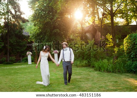 Happy wedding couple is walking down in park