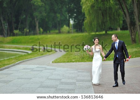 Happy wedding couple walking and having fun in a park together