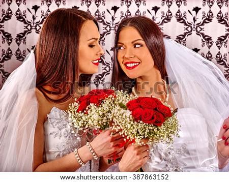 Happy wedding lesbians girls in bridal dress keeps flowers. Indoor. - stock photo