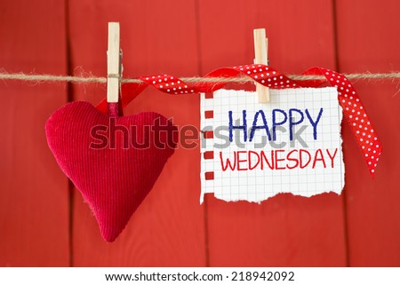 Happy Wednesday on instant paper and small red heart hanging on the clothesline. On red wood background - stock photo