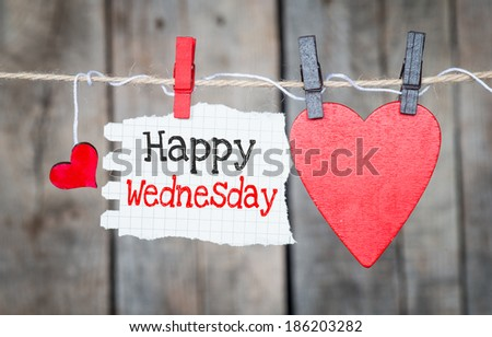 Happy Wednesday on instant paper and small red hearts hanging on the clothesline. On old wood background - stock photo