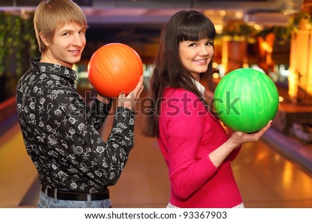 happy wife and husband with balls in bowling club stand sideways to camera - stock photo
