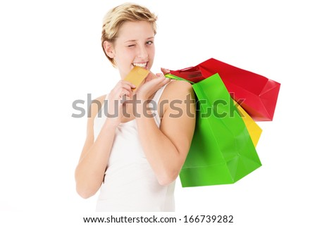 happy winking woman with shopping bags bites on her credit card on white background - stock photo