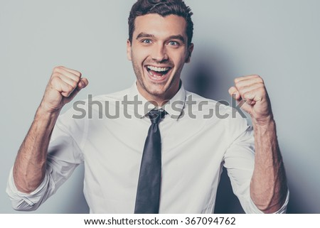 Happy winner. Cheerful young man gesturing and keeping his mouth open while standing against grey background - stock photo