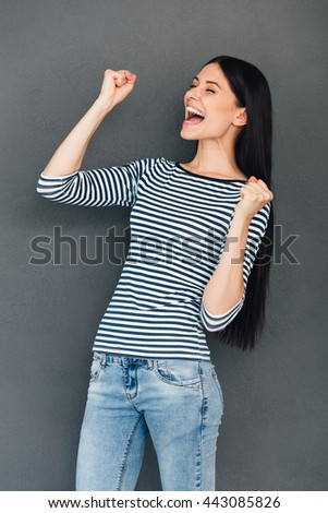 Happy winner. Happy young woman keeping eyes closed and gesturing while standing against grey background - stock photo