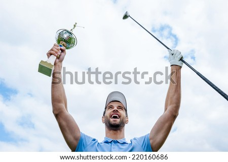Happy winner. Low angle view of young happy golfer holding driver and trophy while raising his arms with blue sky as background - stock photo