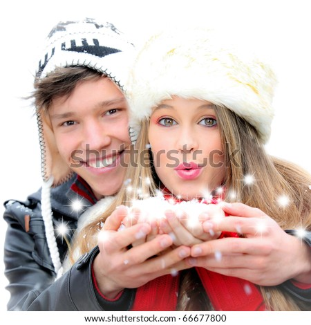happy winter couple blowing greetings wishes with snow flakes - stock photo