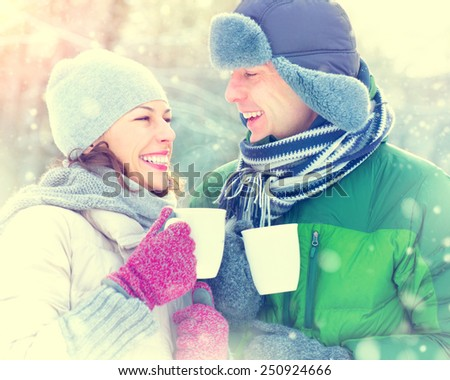Happy Winter Couple drinking hot beverage outdoors. Having Fun in winter park. Snow. Winter Vacation. Hot Drink Outdoor. Joyful family. St. Valentine's Day celebration. Toned photo - stock photo