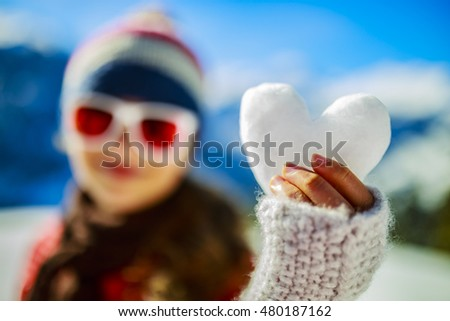 Happy winter girl wearing knitted wear scarf. Excited beautiful smiling teenager playing with  snowball.