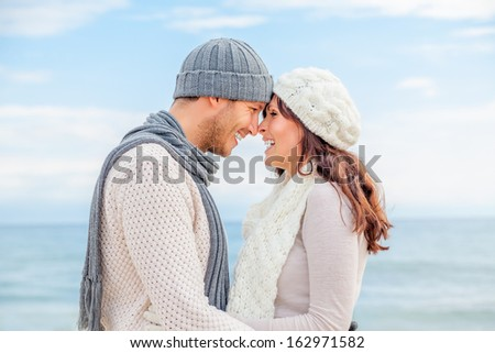 happy winter relaxing couple on the coast kissing - stock photo