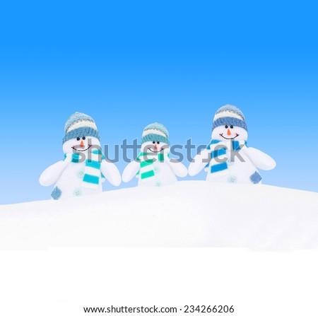Happy winter snowmen family against blue sky background - stock photo
