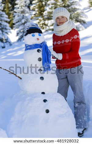 Happy winter teenager girl wearing knitted wear scarf. Excited beautiful smiling teenager playing with snowman and snowball.