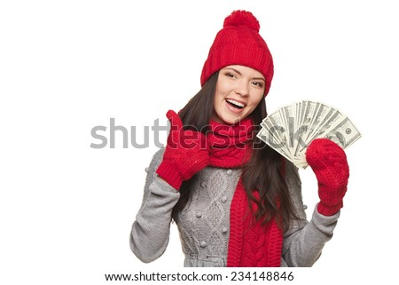 Happy winter woman with us dollar money in hand gesturing thumb up, over white background, with copy space
