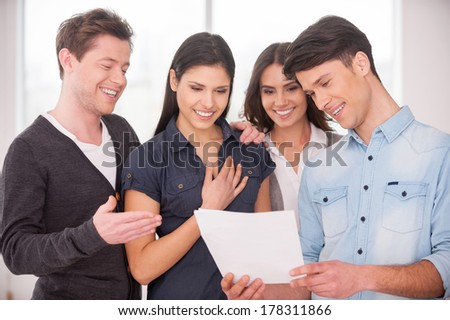 Happy with the result. Group of cheerful young people standing close to each other and smiling while man holding a paper in his hands