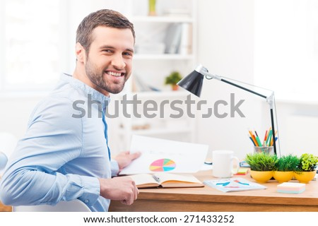 Happy with the results of his work. Handsome young man holding paper with chart and smiling at camera while sitting at his working place  - stock photo