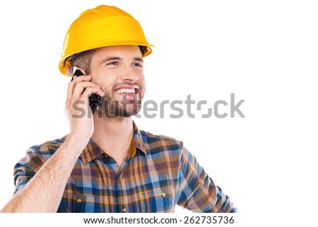 Happy with work done. Happy young male carpenter in hardhat talking on mobile phone and smiling while standing against white background  - stock photo