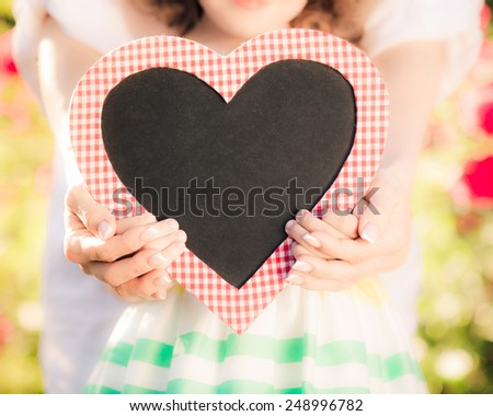 Happy woman and child holding heart shape blackboard blank against spring background. Family holiday concept. Mothers day