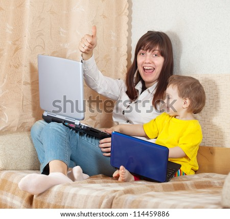 Happy woman and child  sitting on sofa in living room with laptops