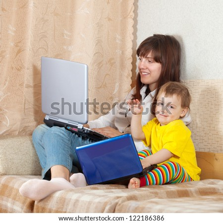 Happy woman and child  sitting on sofa in living room with laptops - stock photo