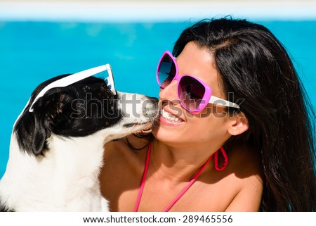 Happy woman and cute dog wearing sunglasses and having fun on summer vacation at swimming pool. - stock photo